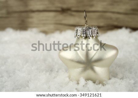 A white star in the snow with wooden background - stock photo