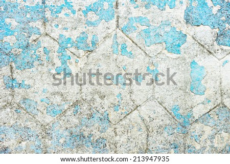 A white stone wall with peeling blue paint - stock photo