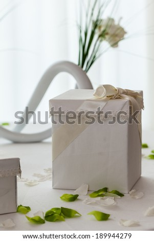 a white table with wedding favors in a big luxurious hall - stock photo