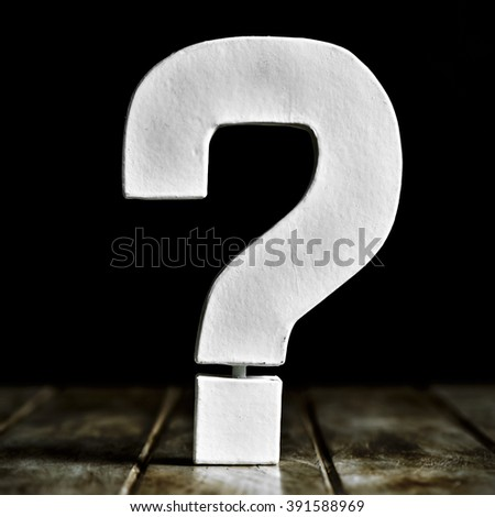 a white three-dimensional question mark on a rustic wooden surface against a black background - stock photo
