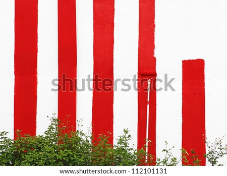 A white wall being painted with red stripes. - stock photo