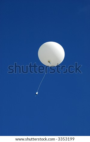 A white weather balloon is ascending into the blue sky. Picture was taken during a 3-month Antarctic research expedition. - stock photo