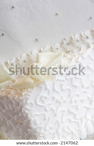 a white wedding cake close-up with neat little swirl details and silver candy buttons - stock photo