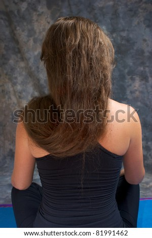 A white woman with long brown hair seen from behind sitting with hair draped over shoulder. - stock photo