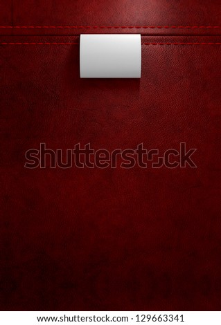 A white  woven clothing label sewn into seamed and stitched red leather - stock photo
