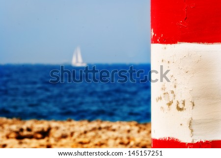 a white yacht seen in the background and out of focus with a bright red and white pillar in the foreground. - stock photo