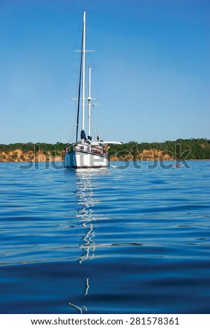 A white yacht sits anchored in the beautiful blue sea off the coast of an island.