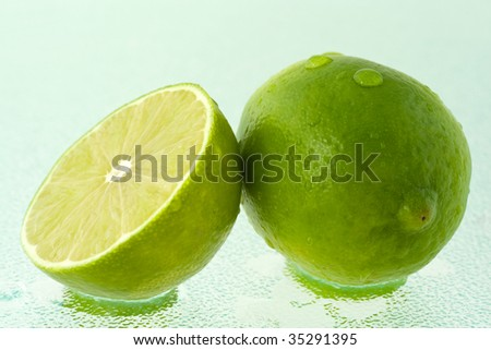A whole green lime and a half, covered by drops of water, on wet glass surface.