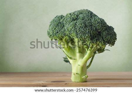 A whole head of raw broccoli on a wood plank table, standing upright on stem against a green background with copy space to the left. - stock photo
