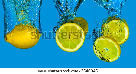 A whole lemon and slices plunging into refreshing cool water - stock photo
