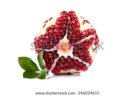 A whole peeled pomegranate with little green leaf on white background - stock photo