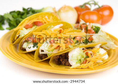 A whole plate of ground beef tacos. Fresh ingredients are shown in the background. Selective focus.