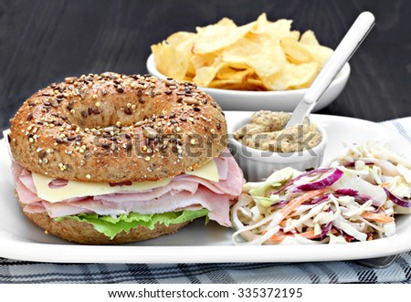 A whole wheat bagel sandwich of ham, swiss cheese and mayo with a side of spicy mustard and cole slaw salad. - stock photo