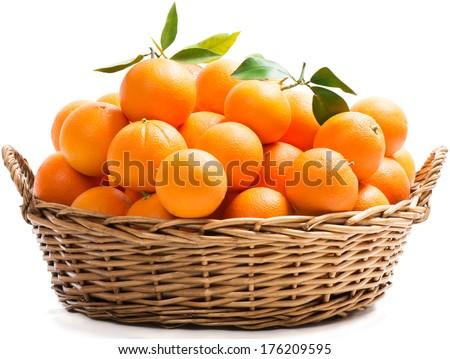 A wicker basket full of fresh orange fruits, isolated on a white background.  - stock photo
