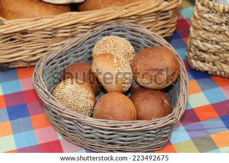 A Wicker Basket of Freshly Made Round Bread Rolls. - stock photo