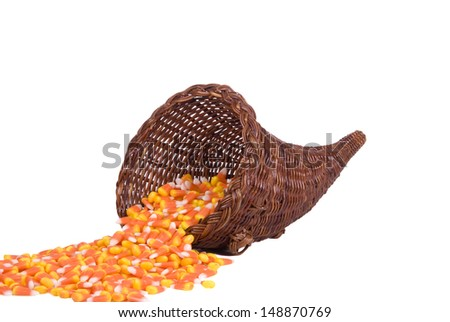 A wicker cornucopia filled with candy corn for Halloween. - stock photo