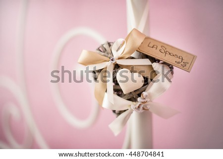 A wicker heart  and ribbon bow hanging from the bed - stock photo