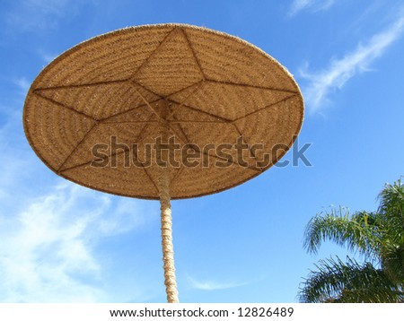A wicker sunshade taken from below with Palm leaves and blue sky and wispy clouds in the background. - stock photo