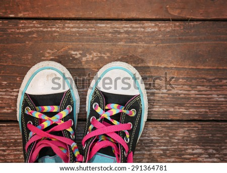 a wide angle photo of a pair of generic looking shoes like converse sneakers with pink shoe laces on a vintage wooden background  - stock photo