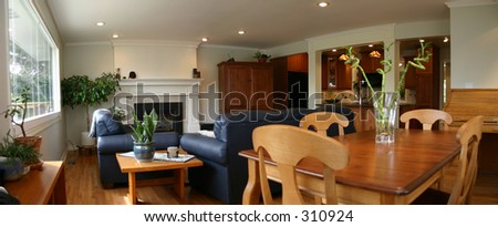 A wide angle shot of a modern great room consisting of a dining table, couches, fireplace, and a kitchen in the background - stock photo