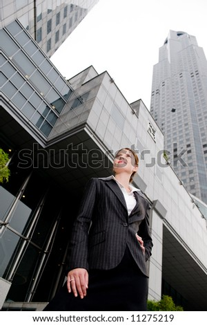 A wide angle shot of businesswoman and skyscrapers - stock photo