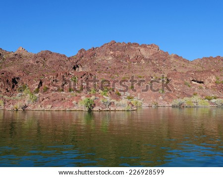 A wide angle view of a vibrant mountainside along a calm lake. - stock photo