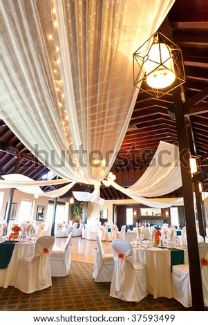 A wide angle view of a wedding reception venue, with dance floor and surrounding tables.  A large chandelier in the middle of the room has tooling draped from it, with mini lights.