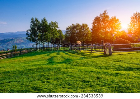 A Wide Angle View of a Wooden Fence Under a Blue Sky with a Beautiful Meadow Blanketed with Wildflowers.  - stock photo