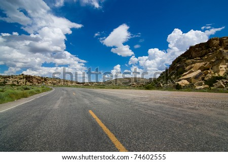 A wide angle view of an American highway stretching through a rocky countryside - stock photo