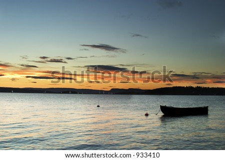 A wide angle view of the sunset on the Oslo fjord, with an old boat in the foreground. - stock photo
