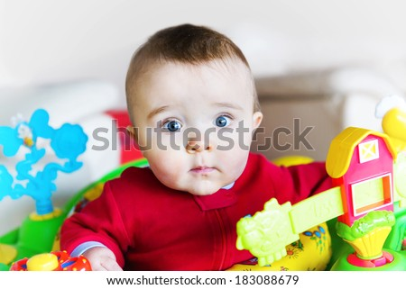 A wide eyed baby boy in a walker or jumper pauses to look at the viewer.   - stock photo