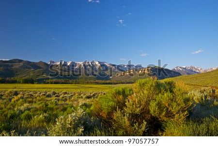 A wide mountain field lays under the mountain's shadow in northern Wyoming. - stock photo
