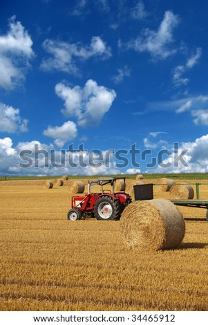 A wide open field showing some bales of straw in front of bright blue sky