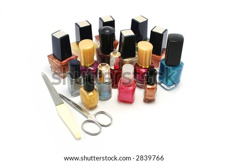 a wide selection of coloured nail varnish/polishes with a small scissors and metal nail file - stock photo