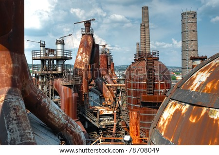 A wide shot of a decaying rusting steel plant with several furnaces and blast chambers. - stock photo