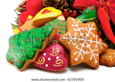 A wide variety of Christmas cookies is against the backdrop of a fragment of a Christmas wreath. All brightly colored cookies. Isolated on white background.