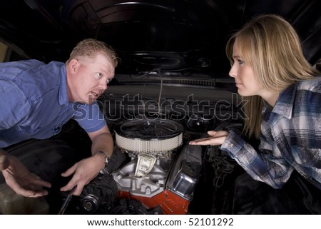 A wife mad at her husband for spending too much money on a car.  He is wondering why she is mad. - stock photo