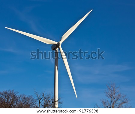 A wind power windmill  turning against a deep blue sky.   Perfect for an article on green or alternative energy. - stock photo