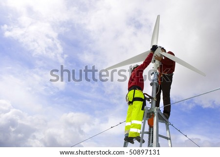 A wind turbine maintenance in a beautiful blue and cloud sky - stock photo