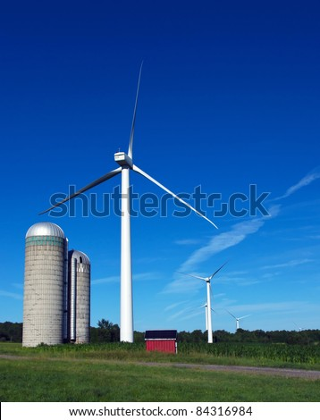 A Wind Turbine next to a farm silo - stock photo