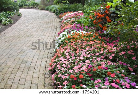 A winding brick path in a flower garden flanked with colorful impatiens and perennials. - stock photo