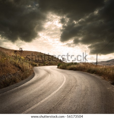 a winding road in countryside with gloomy cloudscape at the sunset - stock photo