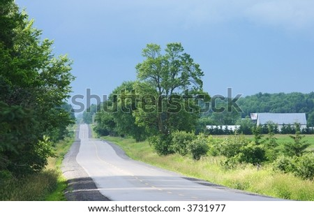 A winding road in rural Ontario. - stock photo