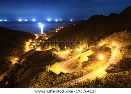 A winding road lit up with lights during the night.