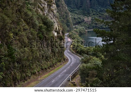 A winding road through a gorge in New Zealand. Wonderful photo for depicting any ideas or concepts about cars, adventure, speed, movement, or the roads we take in life, or many other themes. - stock photo
