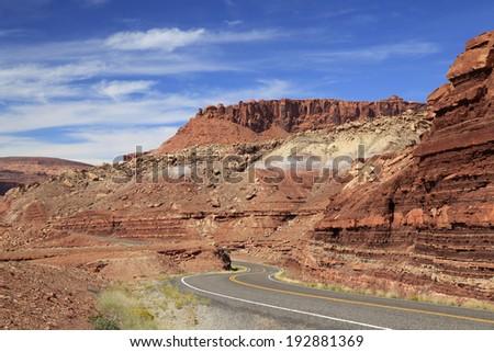 A Winding Road Through Utah's Red Rock Sandstone Desert Landscape - stock photo