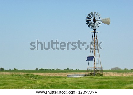 A windmill equipped with a solar power screen on a rural ranch - stock photo