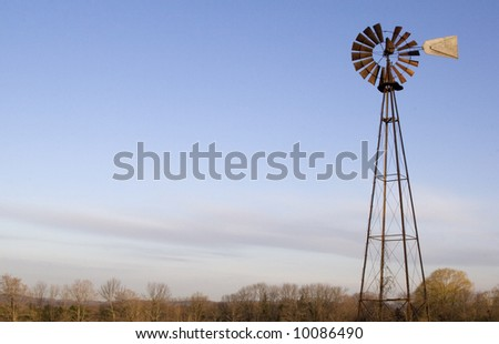 A windmill in a field with a wide open sky behind it. - stock photo
