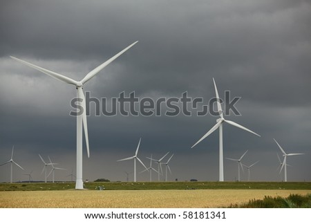 A windmill-powered plant in front of a dark and cloudy sky - stock photo