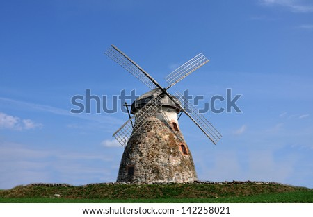 A windmill standing on the hill - stock photo